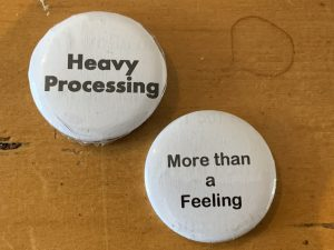 Visual description: two buttons -- white with black letters -- one reads Heavy Processing; the other reads More Than a Feeling.